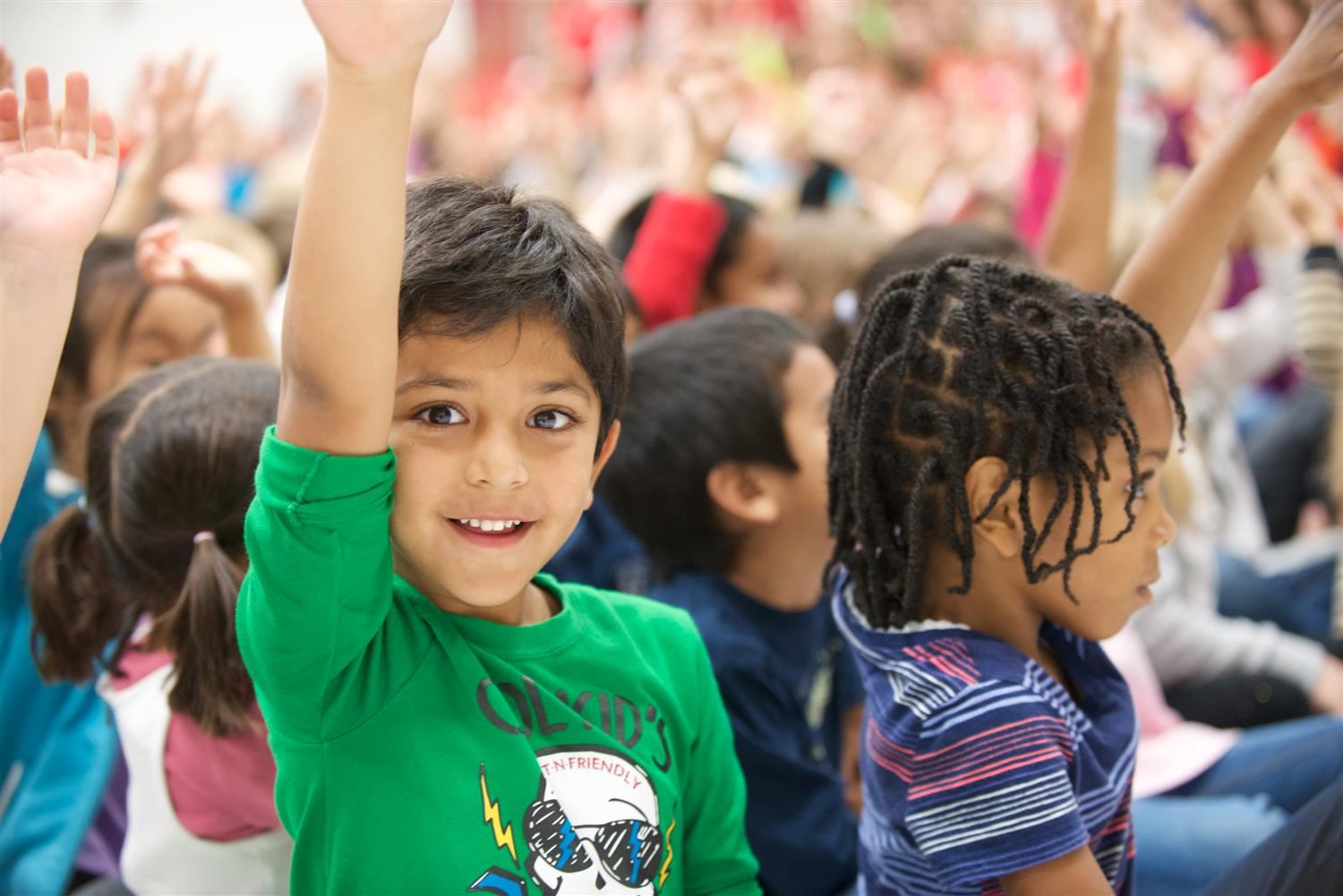 Young boy raising his hand at an assembly