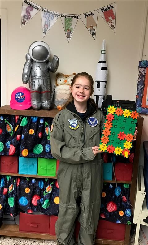 Girl in a flight suit holding a plastic gear toy