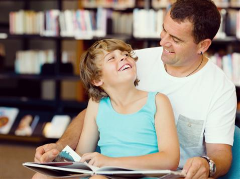 Father and son reading together at library